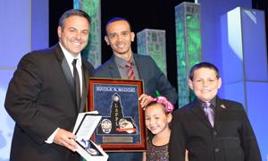 "Gabriel Maldonado (second from left), who served on the founding board of Harbor Area's Teen-Community Police Advisory Board, presents Councilmember Joe Buscaino with the ""In the Line of Duty"" award. Buscaino's children joined him on the stage."